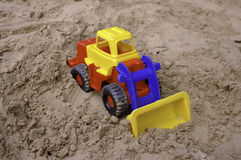Plastic toy tractor on the sand Stock Images