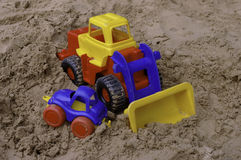 Plastic toy tractor on the sand with the car Royalty Free Stock Photo