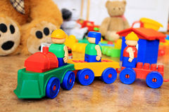 Plastic toy train on colorful background. With teddy bear stock image