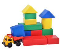 Plastic toy truck with wooden cubes tower. Building process Royalty Free Stock Photo