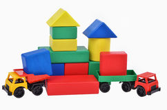 Plastic toy trucks with wooden cubes tower. Building process Royalty Free Stock Image