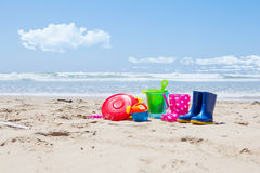 Plastic toys and gumboots on the beach sand Stock Image
