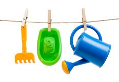 Plastic toys hanged with clothespins. Three plastic toys: yellow rake, green watering can and blue boat hanged on the line with clothespins isolated on white Royalty Free Stock Photo