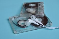 Plastic transparent audio cassette and white vacuum headphones on a bright blue background. Royalty Free Stock Images