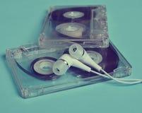 Plastic transparent audio cassette and white vacuum headphones stock photo