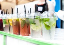 Plastic transparent glasses with different kinds of cold lemonade stays on white table with green border on blurry beach bar stock image