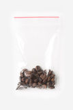 Plastic transparent zipper bag with a little wholegrain coffee beans isolated on white, Vacuum package mockup with red clip. Conce Stock Photography