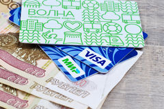 Plastic transport card. And plastic cards of VISA and MIR payment systems on 100 roubles par value paper banknotes on brown background. Russia Volgograd region Stock Images