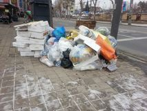 Plastic trash bags filled with garbage sit on the corner of a st Royalty Free Stock Image