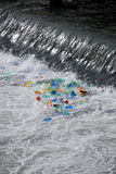 Plastic trash trapped at waterfall. Plastic bottles trapped in the foam at the base of a waterfall.  Taken on the Tiber River in Rome, Italy Royalty Free Stock Image