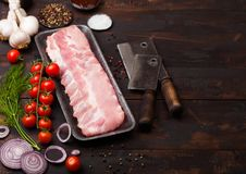 Plastic tray with raw pork ribs and vintage hatchets on wooden background. Fresh tomatoes and red onion with garlic salt and. Pepper stock image