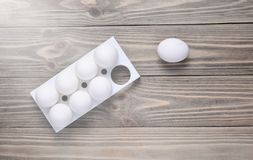 Plastic tray with white eggs on wooden table, minimalism trend,. Top view royalty free stock photos