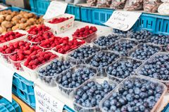 Plastic trays with fresh blueberries and raspberries. Counters on the street market in Prague, Czech Royalty Free Stock Image
