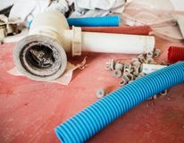 Plastic tubes, plugs and clogged drain on a red table stock image