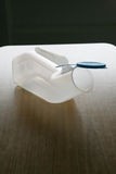 Plastic urinal on a table Royalty Free Stock Image