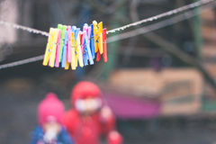 Plastic varicoloured clothes pins on the rope in spring rainy day Royalty Free Stock Photos