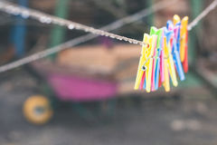 Plastic varicoloured clothes pins on the rope in spring rainy day Stock Images