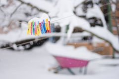 Plastic varicoloured clothes pins on the rope in winter snowy day Stock Photography