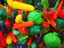 Plastic vegetables for preschoolers - foodstuff teaching material. Colorful and various vegetables wrapped in nets royalty free stock photos