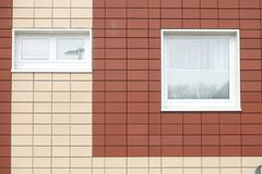 Plastic vensters op o-huismuur Stock Foto