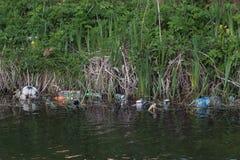 Plastic verontreiniging - plastic flessen, pakketten in de rivier royalty-vrije stock foto