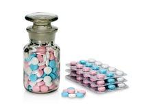 Plastic verpakking en glasflesje met pillen van verschillende kleur. Royalty-vrije Stock Foto's