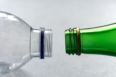 Plastic versus Glass Bottles. Closeup of bottlenecks in plastic and glass opposite each other royalty free stock image