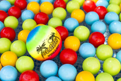 Plastic volleyball swimming between many colorful plastic balls royalty free stock photo