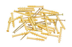 Plastic wall plugs and chipboard screws on a light background. Pile of yellow plastic wall plugs and zinc plated chipboard screws with countersunk heads on a Stock Photography