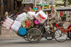 Plastic ware vendor driving his bicycle in Phnom Penh Stock Photography