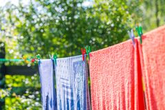 Plastic washing line and clothespins on natural background. Clothespin hanging on washing line. Plastic washing line and clothespins on green nature background Royalty Free Stock Photo
