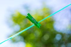 Plastic washing line and clothespins on natural background. Clothespin hanging on washing line. Plastic washing line and clothespins on green nature background Royalty Free Stock Photos