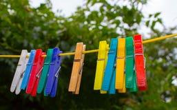 Plastic wasknijpers die op een drooglijn hangen Stock Foto