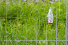Plastic waste is disposed of irresponsibly on wire cage Royalty Free Stock Photography