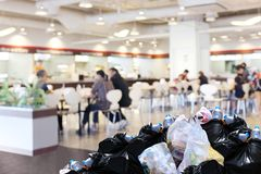 Plastic waste garbage bag black bin full Lots pile of junk at front canteen food court mall department store background, pollution. The plastic waste garbage bag Royalty Free Stock Image