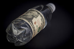 Plastic water bottle with pasted dollar bill. Background, Isolated Stock Photography