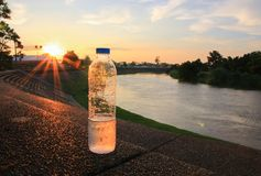 Plastic water bottle on the stone floor in a public park at sunset, sunrise time royalty free stock photography