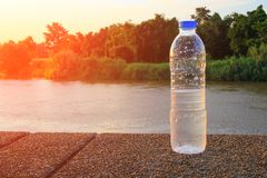 Plastic water bottle on the stone floor in a public park at sunset, sunrise time stock images