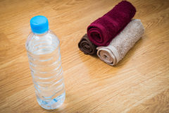 Plastic water bottle and towel on the wooden table Royalty Free Stock Photography