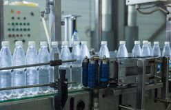 Plastic water bottles on conveyor and water bottling machine industry. Stock Photography