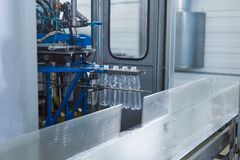 Plastic water bottles on conveyor and water bottling machine industry. Stock Image