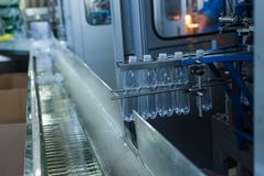Plastic water bottles on conveyor and water bottling machine industry. Stock Images