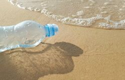 Plastic water bottles pollution in ocean on the shore,