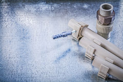 Plastic water pipe fixtures connectors on metallic background co Royalty Free Stock Photo
