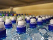 Plastic waterflessen met kappen van verschillende kleur stock afbeeldingen