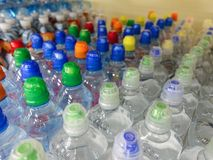 Plastic waterflessen met kappen van verschillende kleur stock fotografie