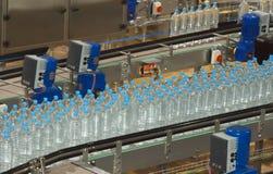 Plastic waterflessen op transportband Stock Afbeeldingen