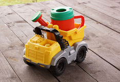 Plastic watering can in the back of the toy car. Royalty Free Stock Images