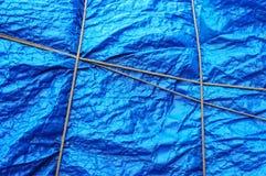 Plastic waterproof tarpaulin with rope Stock Images
