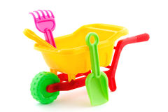Plastic wheel barrow toy. Yellow plastic wheel barrow toy filled with garden rake and garden shovel Stock Images